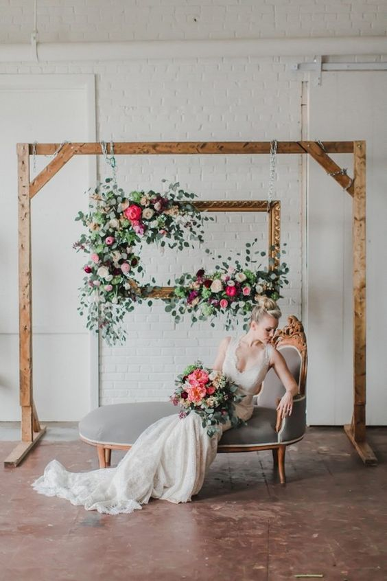 a wedding lounge with a refined daybed and a hanging frame with lush blooms for shooting weddign portraits