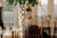 11 an elegant centerpiece with white blooms and greenery and silver ornments inside the vase