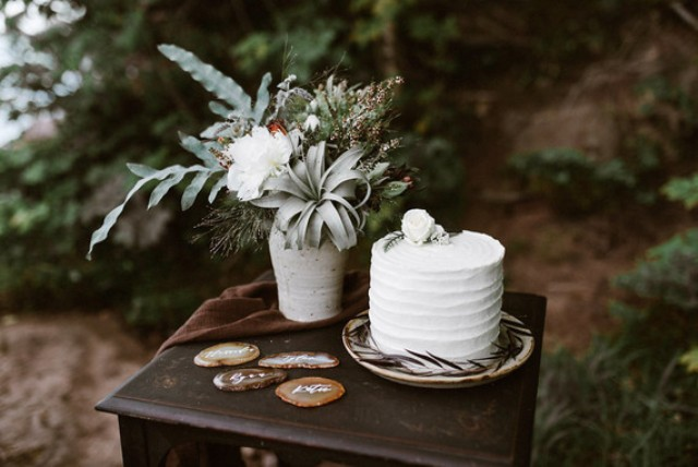 The wedding cake was a white one with a white flower on top, the arrangement next to it is made of greenery, white blooms and an air plant