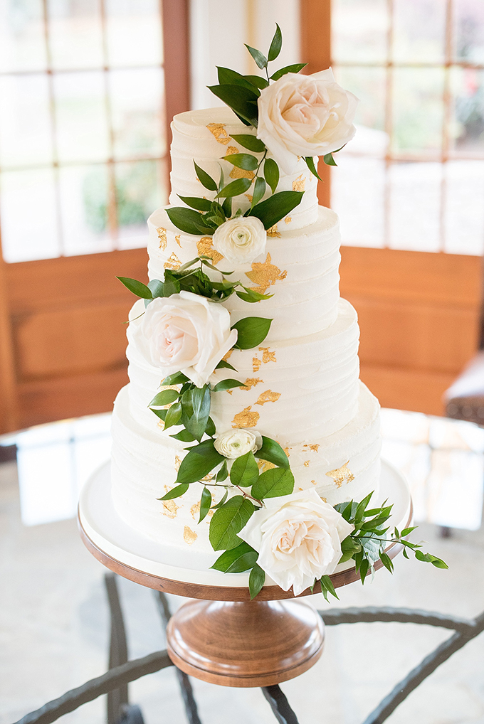 The wedding cake was a white one with gold leaf and white and blush blooms and greenery