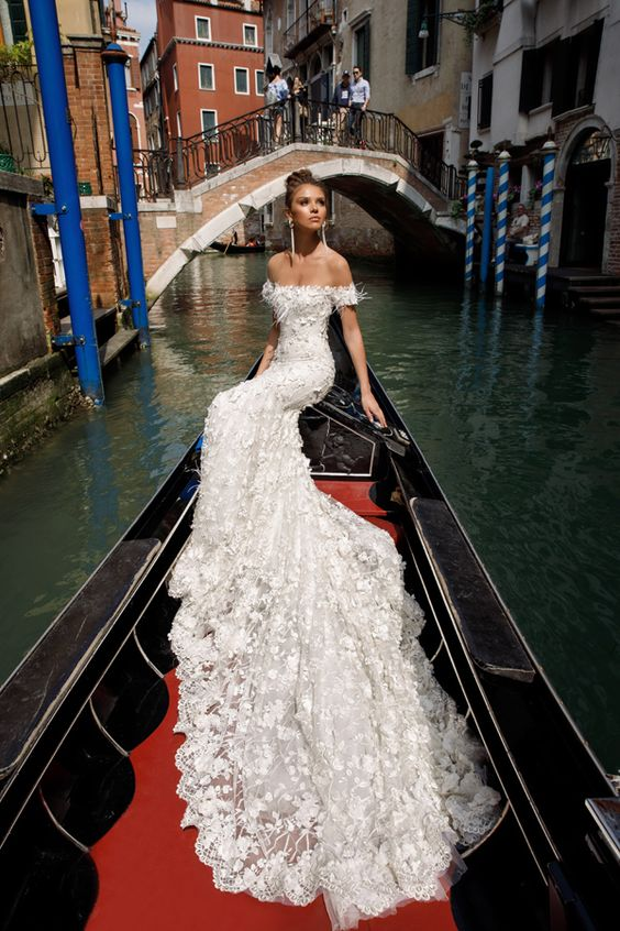 a bride wearing an off the shoulder lace applique wedding dress with a long train and statement earrings