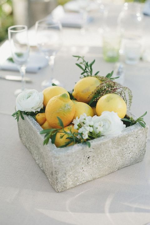 a concrete box with lemons, foliage and white blooms for a modenr tropical wedding