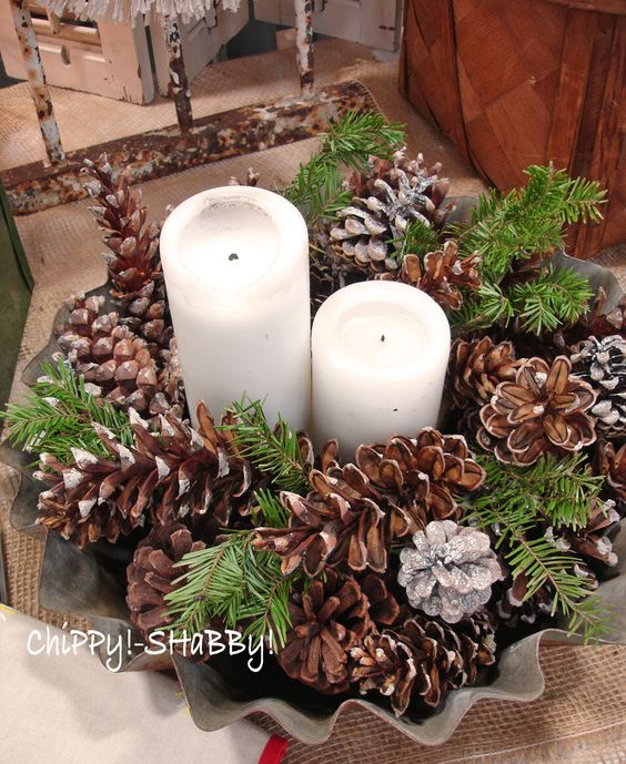 a lush centerpiece with snowy pinecones, evergreens and pillar candles