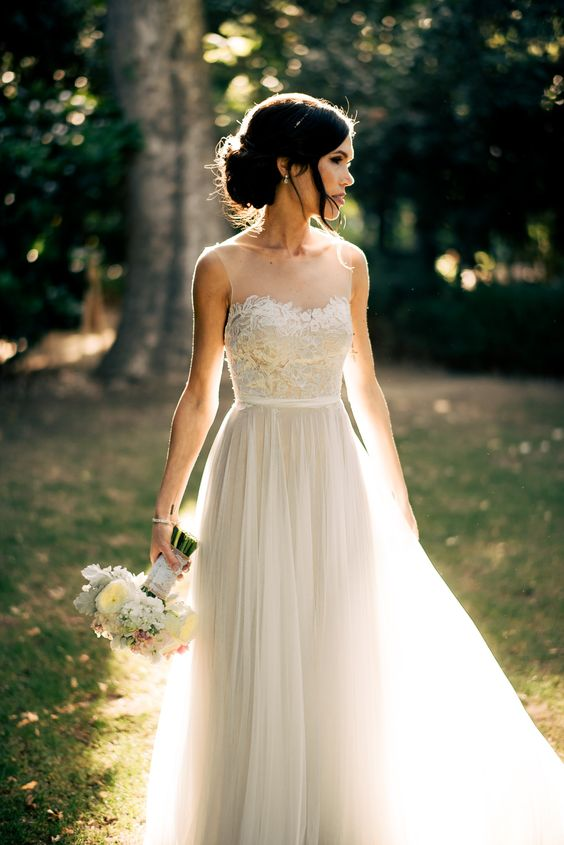ethereal sleeveless wedding dress with a lace applique bodice, a faux sweetheart neckline and a layered skirt