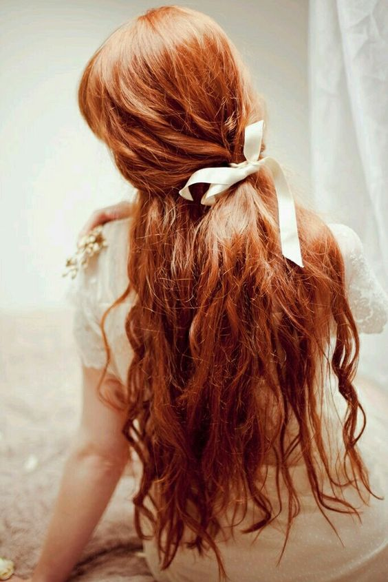 long wavy red hair with a poytail incorporated and a creamy bow for a romantic bride