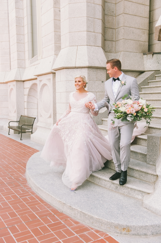 a blush wedding gown with an illusion neckline, long sleeves and white lace appliques