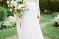 13 a textural lace bodice with long sleeves and a high neckline and a flowy skirt