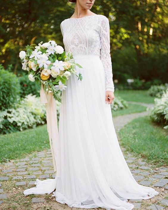 a textural lace bodice with long sleeves and a high neckline and a flowy skirt