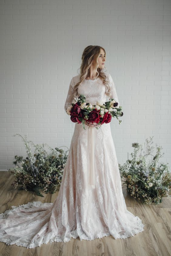 a blush wedding dress with white lace appliques, a train and long sleeves looks feminine
