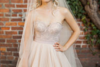 a gorgeous strapless sweeteheart neckline blush wedding dress with an embroidered bodice and a layered skirt and a matching veil