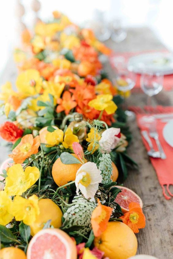 a lush table runner with oranges, pomegranates, orange annd yellow blooms looks very bold