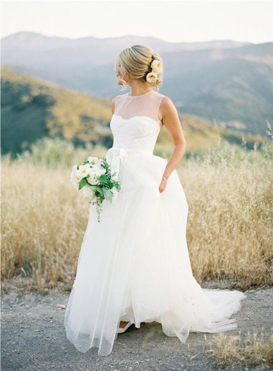 a modern wedding gown with an illusion sweetheart neckline, no sleeves and a layered skirt