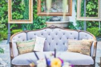 14 a wedding lounge with a lilac sofa and hanging picture frames over it for a chic feel