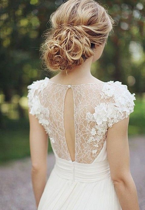 a cute feminine wedding dress with lace appliques, draping and a cutout detail on a button
