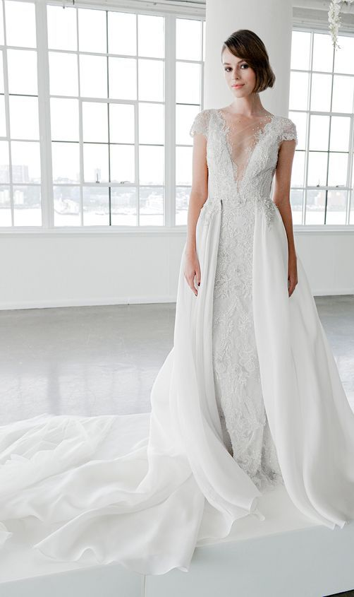 a lace A-line wedding dress with an illusion neckline, cap sleeves, and skirt overlay