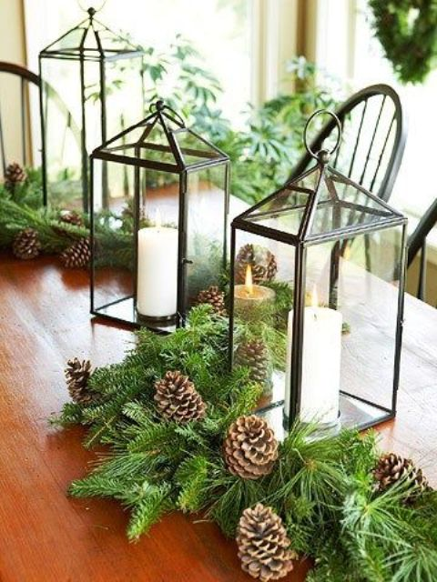 a lush evergreen table runner with pinecones and candle lanterns