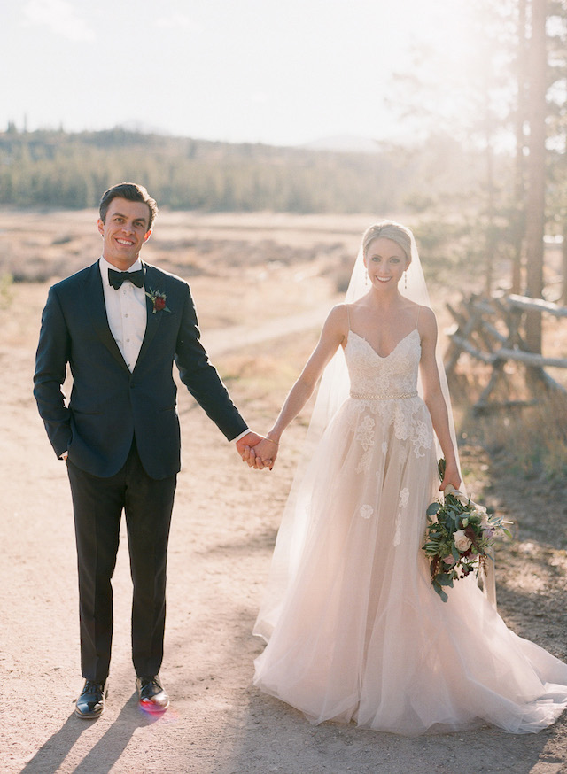 a spaghetti strap wedding dress with a lace applique bodice and a layered skirt