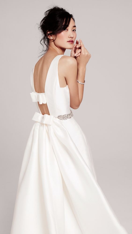 a gorgeous plain wedding dress with an embellished belt, a cutout back and bow detailing