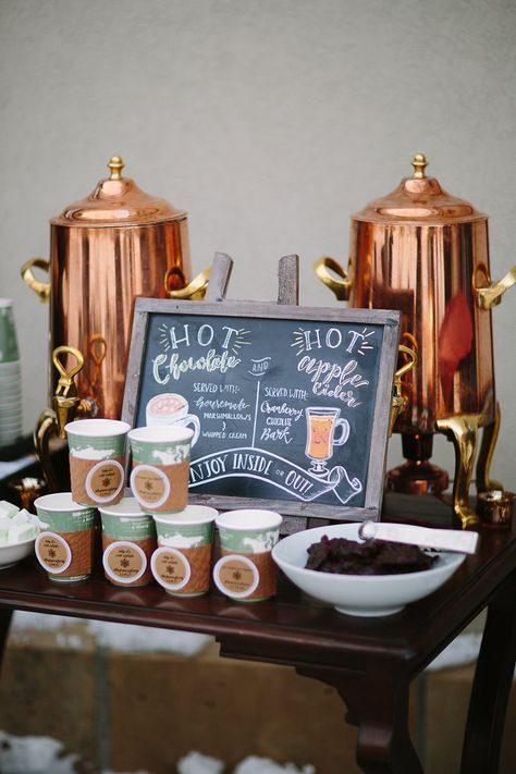 a hot chocolate bar is decorated with copper tanks and a chalkboard sign for a cozy winter look
