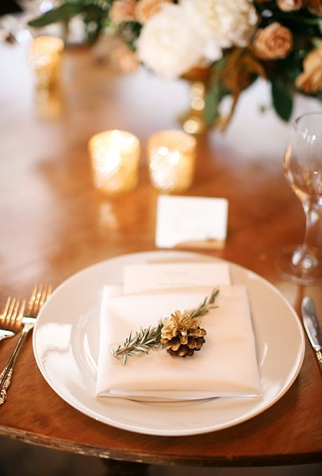 a place setting with evergreens and a gilded pinecone for a winter feel