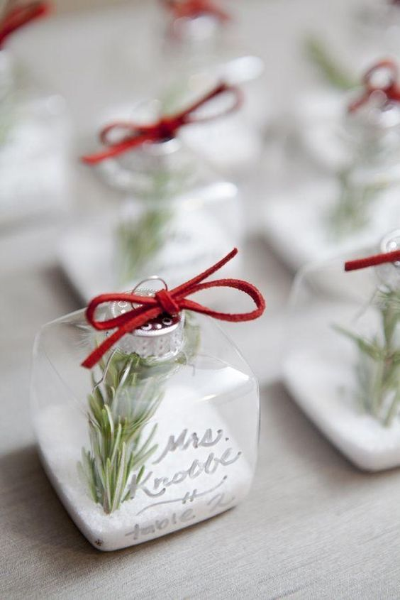 glass ornaments filled with faux snow, rosemary and with names on them can be place cards and favors