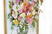 17 a gilded frame with an artwork completed with fresh blooms looks really wow