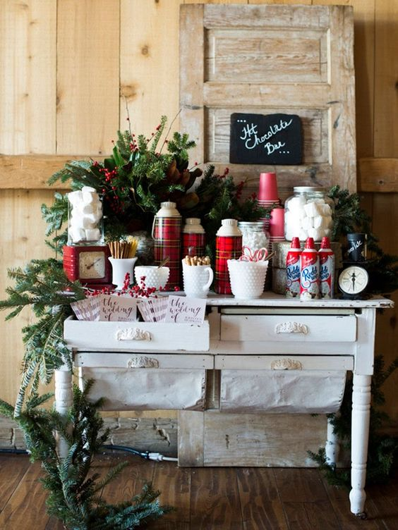 a gorgeous hot chocolate bar with an evergreen garland, plaid thermoses, lots of sweets for eating them