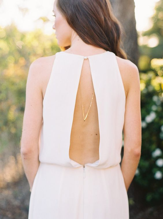 a modern sleeveless wedding dress with a cutout back and a necklace to highlight it