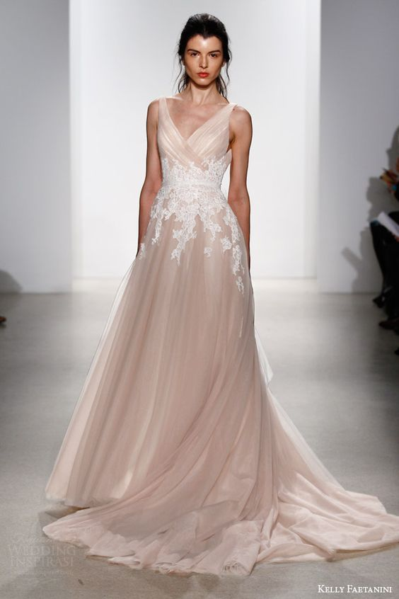 a sleeveless blush wedding dress with white lace appliques on the waist line and a train