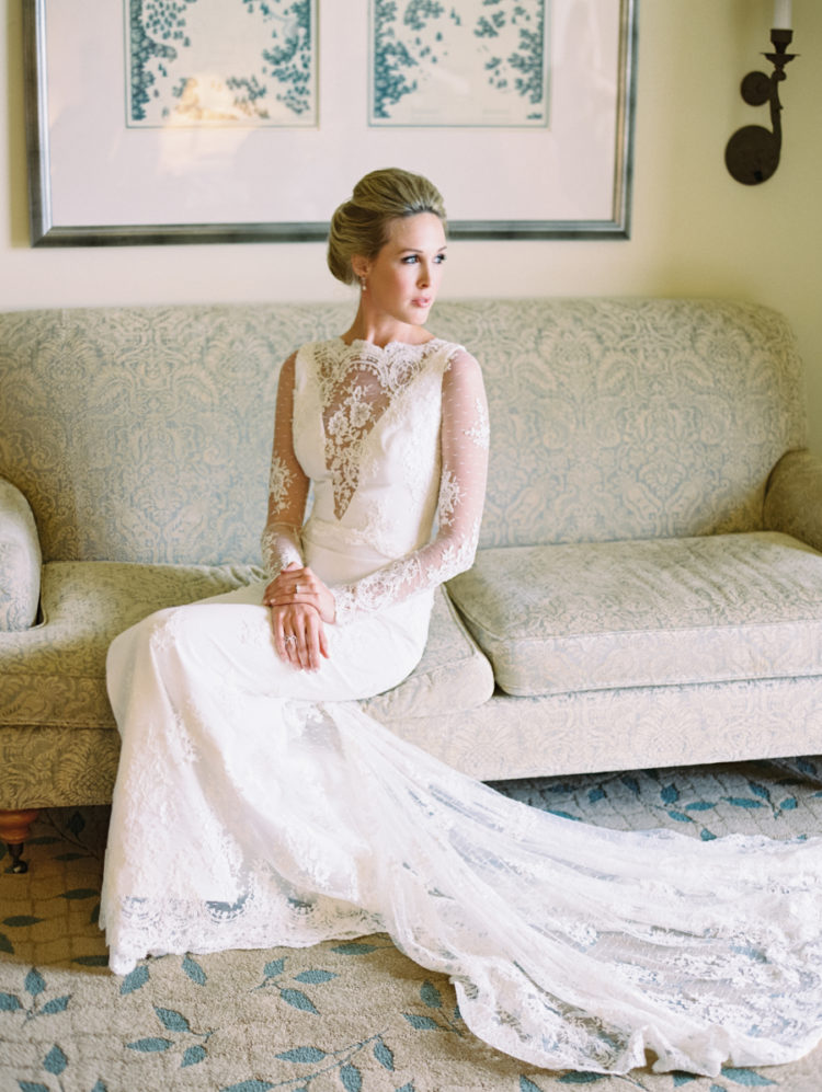 long sleeve lace wedding dress with an illusion plunging neckline and a long train