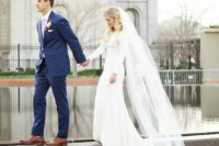 18 a modern plain wedding dress with long sleeves and a train, and a veil to make the look more romantic