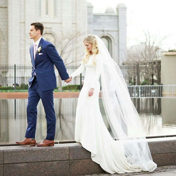 a modern plain wedding dress with long sleeves and a train, and a veil to make the look more romantic