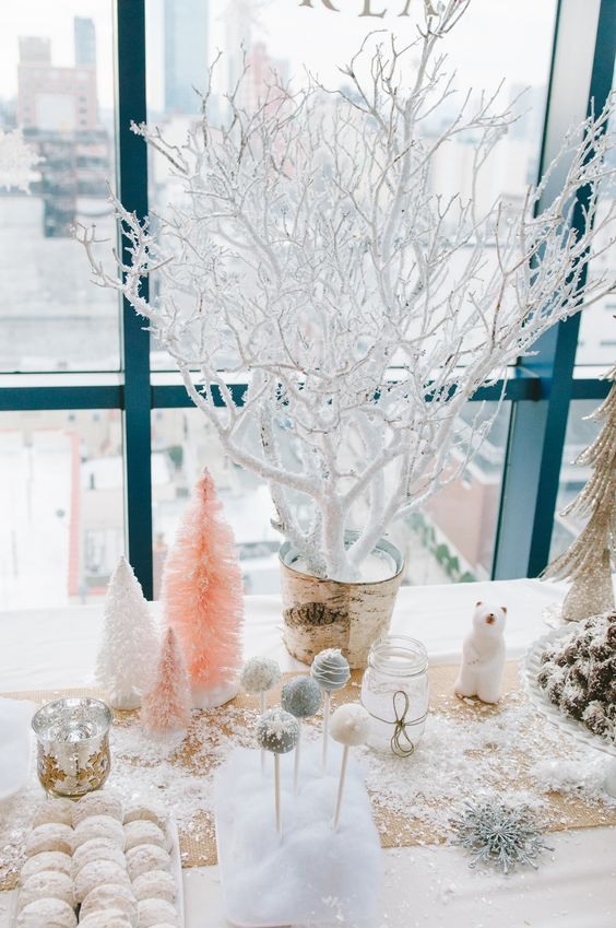 a snowy dessert bar with iced branches, pastel Christmas trees and snowflakes
