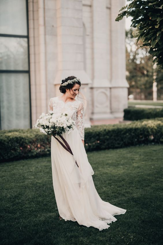 a wedding dress with three quarter sleeves, a textural lace bodice and a flowy and airy layered skirt