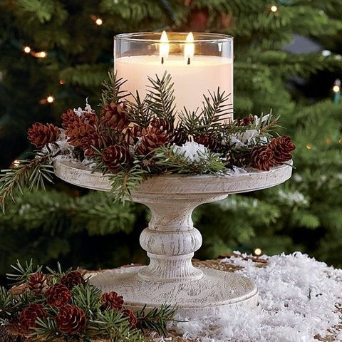 a winter wedding centerpiece with evergreens, pinecones, faux snow and a large double candle