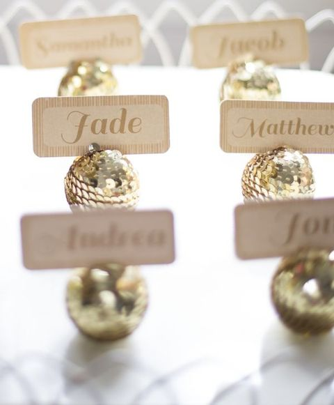 gold sequin ornaments with place cards held is a cool and glam idea for a winter wedding