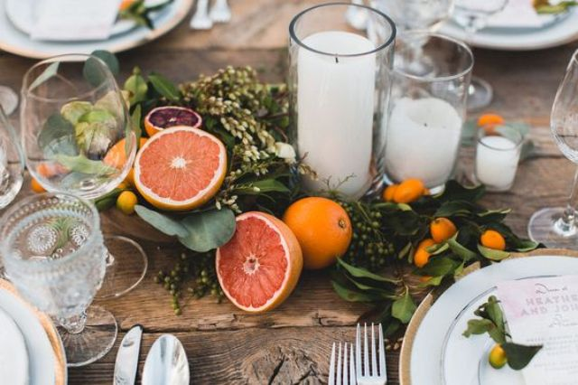 stylish wedding table decor with foliage, citrus and some candles in the center of the table