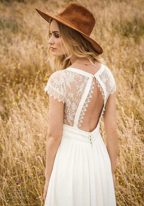 a boho wedding dress with an illusion lace bodice, a cutout back and a plain skirt