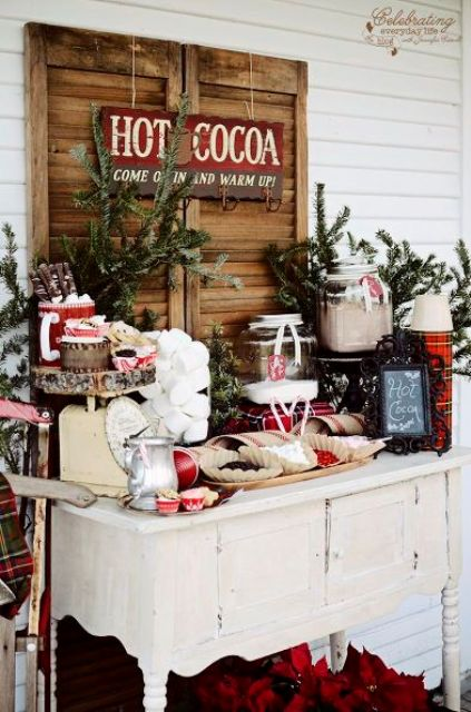 a hot cocoa bar with a vintage dresser, fir branches, plaid touches and lots of various candies