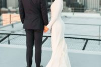 19 a modern wedding dress with a high neckline, long sleeves and a textural ruffled train