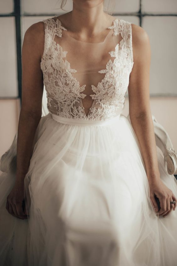 an illusion plunging neckline sleeveless wedding dress with a lace applique bodice and a tulle skirt