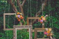 19 various bloom topped picture frames hanging from above for a photo booth
