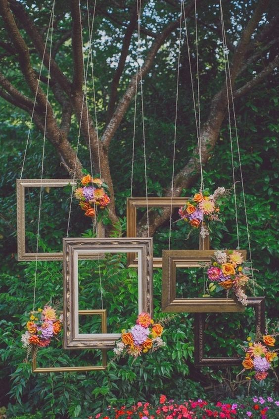 various bloom topped picture frames hanging from above for a photo booth