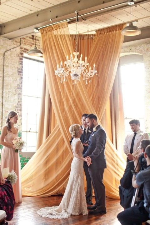 a draped fabric backdrop and a glam chandelier for a refined look