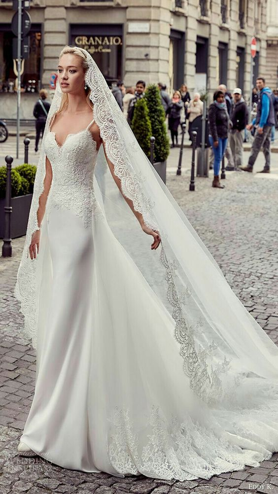 a sheath wedding dress with spaghetti straps, a lace bodice, a plain skirt with a train