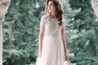 21 a bateau neckline wedding dress with a lace applique bodice, short sleeves and a plain A-line skirt