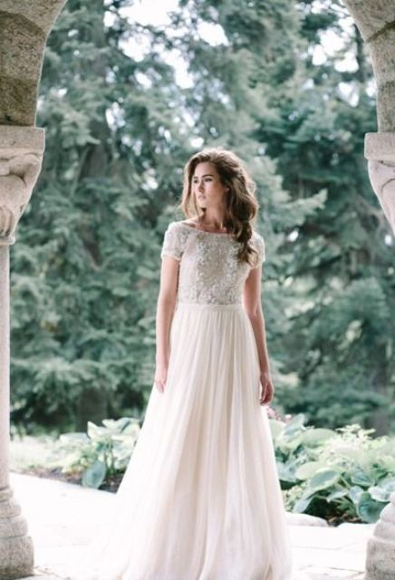 a bateau neckline wedding dress with a lace applique bodice, short sleeves and a plain A-line skirt