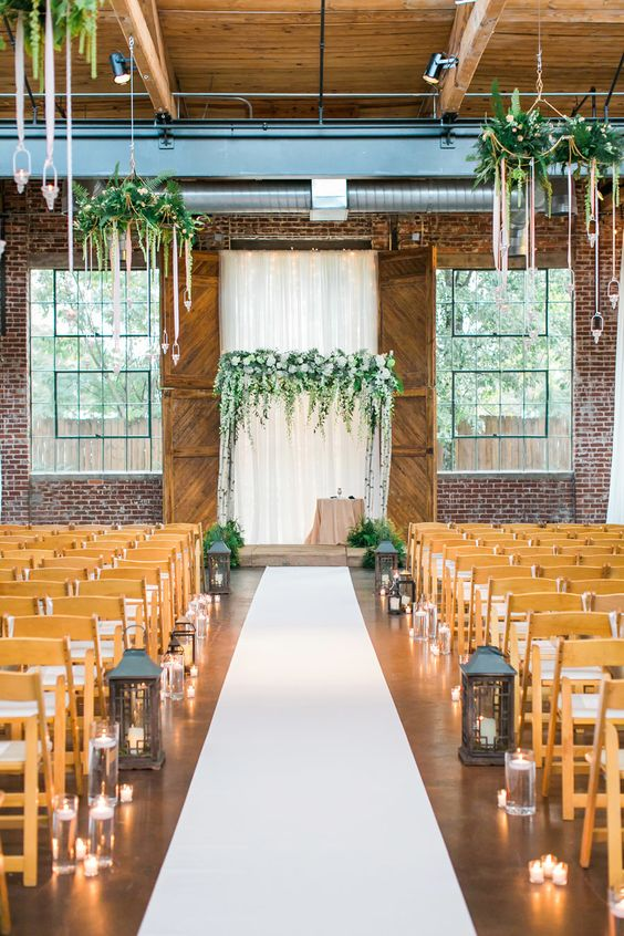 a draped fabric backdrop, a lush greenery and white bloom arch and greenery chandeliers hanging over it