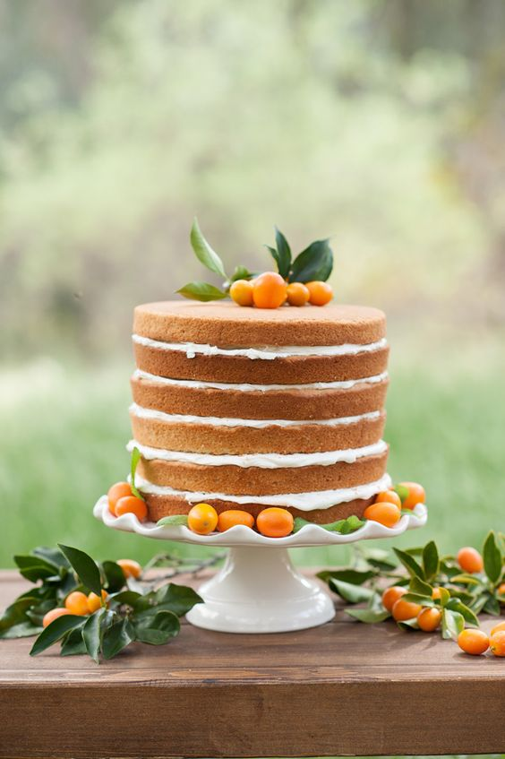 a naked wedding cake topped with kumquats for a bold summer wedding