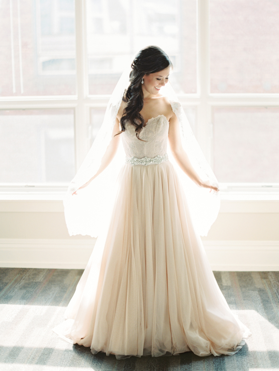 a strapless blush wedding dress with a lace embroidered bodice, an embellished belt and a matching veil